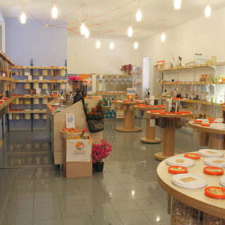 The photo shows round tables and shelves arranged on a tiled, gray colored floor. The furniture is made of light-colored wood and is displaying kitchen products and foods stored in clear jars with white and orange tops. There are small vases with bright pink flowers around the place. On the ceiling, tubular glass lamps are connected to each other by orange wires. The walls are sand colored, with the exception of one in the back, in the left corner of the photo, that has a blueish-gray tone.