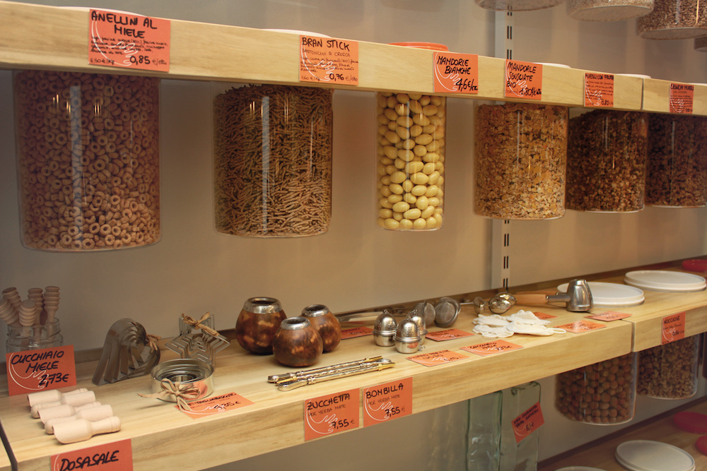 The photograph shows two shelves that are part of a wooden rack. On the higher one are transparent cylindrical containers, suspended side by side, containing different types of grain. On the lower one are various kitchen utensils. On the front edge of the shelves, facing the camera, are orange stickers with the price and name of each product in Italian, written in black.