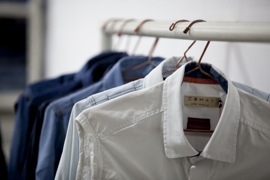 "Shirts hanging on a metallic rack, on a gradient from white to dark blue, with the white shirt closest to the camera, displaying a beige label with the brand ""Comas - São Paulo"" written in black. In the background is a white wall."