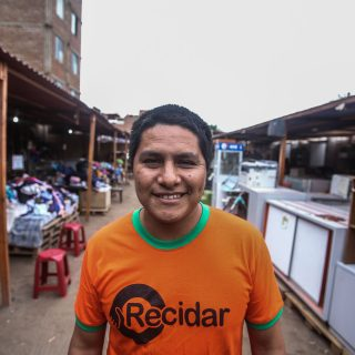 "A Peruvian man, with brown skin, smiles at the camera. He has short, dark straight hair and is wearing an orange t-shirt with a green collar, with the ""Recidar"" logo printed in black on the chest. Around him and in the back are stands with furniture and items of clothing arranged in them, and a gray sky."