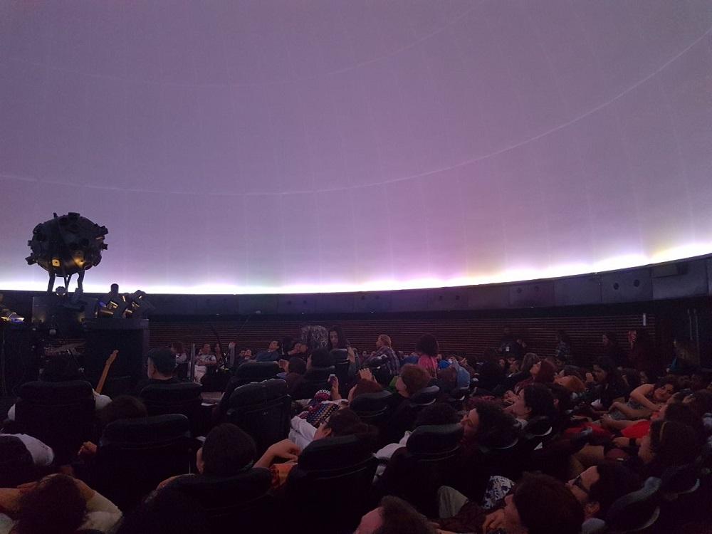 Pessoas em bancos escuros reclinados assistem a uma exibição em uma tela semi-esférica afixada no teto. Na tela, um fundo azulado é contornado por uma linha fina luminosa. No canto esquerdo central da foto, há um aparelho esférico de projeção de imagens.