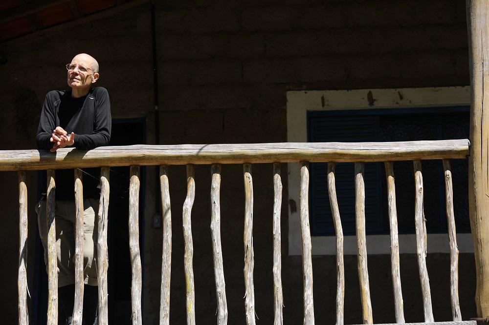 Una señora rapada, de piel blanca, en el lado izquierdo de la foto, apoya los antebrazos en la barandilla de madera natural de un balcón amplio. La señora lleva gafas de lentes redondas, montura fina plateada, una camiseta negra de manga larga y un pantalón beige, doblado hasta debajo de las rodillas. Está de frente a la cámara y mira al horizonte, diagonalmente y a la izquierda de la foto. Al fondo, hay una pared de ladrillos, una puerta con marco azul abierta y una ventana de madera azul y marco blanco ancho, a la derecha. La luz del sol incide en la barandilla, iluminando también el rostro de la señora, mientras que la pared del fondo está a la sombra.