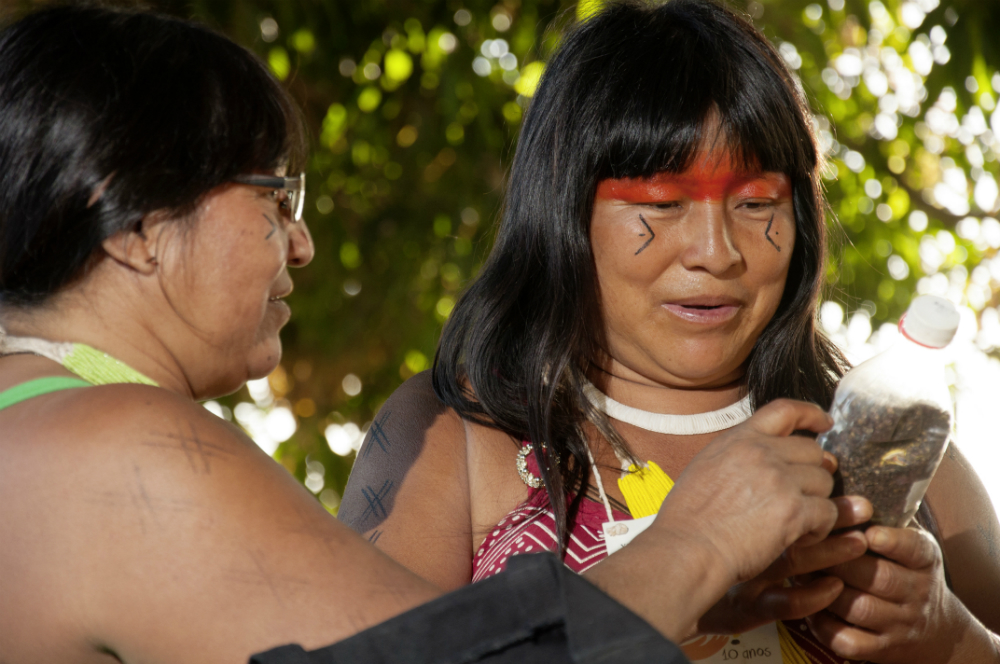 Two indigenous women are having a conversation. The woman on the left of the photo is in profile, pointing to an object in the other woman's hands, who is looking at it and facing towards the camera. The woman on the left is wearing black-rimmed glasses and has straight black hair that is cut-off by the photo's left margin. The woman on the right also has long, straight black hair with bangs that cover her forehead. She is wearing a white necklace, and has a red band of paint across her face that goes over her eyelids and eyebrows. Below each of her eyes is a drawing of half a diamond shape with a dot at the center and the tips facing inwards toward her nose. She is holding a small, clear plastic bottle filled with earth and with a white cap.
