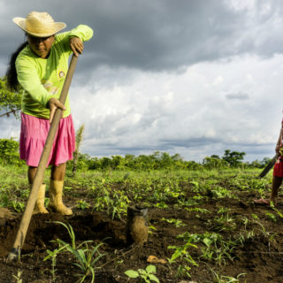 Near the left edge of the photo, an indigenous woman facing the camera is holding a large hoe that is digging into the earth in front of her. She has long, straight dark hair in a ponytail, and wears yellow rubber boots, a pink skirt down to her shins, a lime green long-sleeved shirt and a straw hat. In the right side of the photo, an indigenous girl watches the woman work, her left hand resting on her hip. She has long, straight dark hair with bangs that cover her forehead. She is wearing a flower print dress that is yellow and red, with red trim and a red band at the hip, and pink flip-flops. The woman and girl are standing on soft, dark earth and thin green grass. In the back is a cloudy sky.