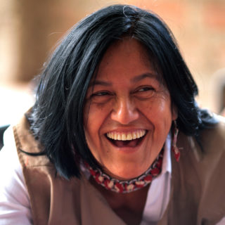 The photo shows the face of a woman with bronze skin, straight black hair down to her shoulders and dark brown eyes. She is wearing a light brown vest over a white shirt and has a red necklace. The woman is facing the camera but is looking off to the right of the photo. She has a wide open smile, exposing her upper teeth.