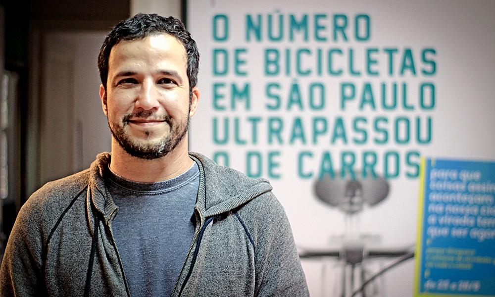 """El mismo hombre de la foto de portada, de piel blanca, pelo corto castaño oscuro y barba corta, mira a la cámara con una ligera sonrisa con la boca cerrada. Lleva una camiseta gris por debajo de una chaqueta, también gris, cerrada con cremallera hasta la altura del pecho. La chaqueta tiene capucha. Detrás de él, y al lado derecho de una puerta, hay un cuadro grande de fondo blanco en el que está escrito: """"El número de bicicletas en São Paulo ha superado al de coches"""", en verde agua. Debajo de ese escrito está la imagen de una antena parabólica gris desenfocada. A la misma altura de esta imagen, delante del cuadro, a la derecha, hay un cartel azul celeste con texto ilegible (desenfocado) con letras blancas y amarillas."""