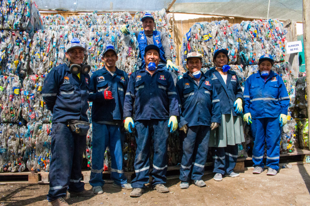 Men and women in uniform, wearing dark blue caps, pants and long-sleeve shirts with thick work gloves pose for a photo. They are also wearing blue face masks, hanging by their necks, and some of them are smiling. All have bronze skin and dark hair. The ground is made of gray cement. Behind them are piles of recyclable plastic material stacked on wooden pallets.