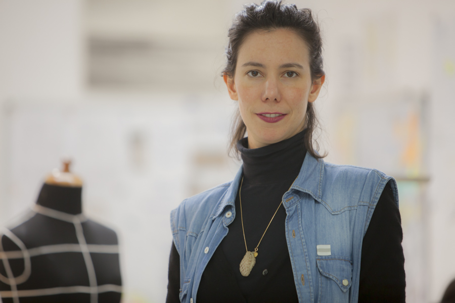 A woman looks at the camera. She has white skin, straight dark brown hair tied back, a gold chain necklace with a round beige pendant, and is wearing a black turtleneck shirt under a light blue denim vest. On the left of the photo is a black bust mannequin with white lines. The background of the photo is white and out of focus.
