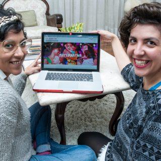 """Dos mujeres sentadas sobre una alfombra blanca miran por encima de sus hombros en dirección a la cámara, sonriendo y mostrando la pantalla de un computador portátil, abierto encima de una mesa baja, de mármol blanco, que está en el centro de la foto. La pantalla muestra una foto con mujeres que llevan bebés en brazos y la palabra """"Maternativa"""" (de maternidad y """"locomotiva""""; que quiere decir locomotora en español), en letras blancas. La mujer del lado izquierdo lleva gafas de pasta transparentes, con lentes grandes, redondeadas, y pendientes blancos en forma de rectángulos. Tiene el pelo corto, rizado, castaño oscuro, sujeto por una cinta con estampado de leopardo, y viste un jersey de lana gris claro de manga larga y un pantalón jean. La mujer de la derecha tiene el pelo ondulado castaño, por encima de los hombros, y viste camiseta negra con estampa étnica geométrica en gris claro."""