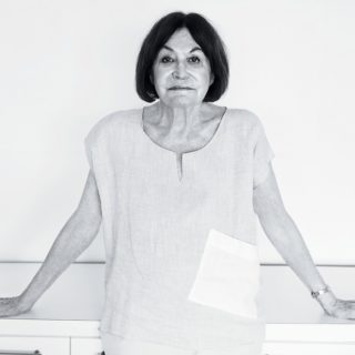 A black and white photo shows a woman with light skin, dark eyes, straight dark hair down to her shoulders, looking at the camera and resting her back and hands, her arms half open symmetrically, on a white cabinet. She is wearing a loose light colored shirt with short sleeves and a metallic bracelet on her left wrist. Behind her is a white wall.