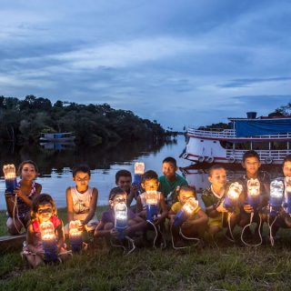 Several children are crouching on a lawn, facing the camera, while holding lamps built out of the lower half of plastic bottles, fitted onto blue electrical holders. In the background, on the right side, is a small boat anchored in a river, and a slightly cloudy sky at dusk.