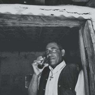 A black and white photo of a man facing diagonally towards the left of the camera, leaning against an open wooden door, which is closer to the right of the photo, white holding a small glass with a dark liquid in it close to his closed mouth. The man has dark skin, short dark hair, and is wearing rectangular wire frame glasses, its lenses reflecting some light. He is wearing a black vest over a white shirt and has a chain around his neck with a medium size cross pendant. The interior of the house can be seen through the doorway in the background.