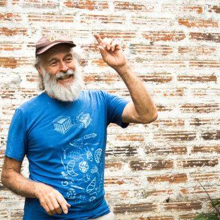 Um senhor, virado diagonalmente para o canto direito da foto, sorri e levanta seu braço esquerdo, com o dedo indicador apontando para cima. Ele tem pele branca, barba e bigode cheios e cabelos lisos brancos. Usa uma boina marrom e uma camiseta azul turquesa com estampas brancas. Ao fundo, uma parede de tijolos.