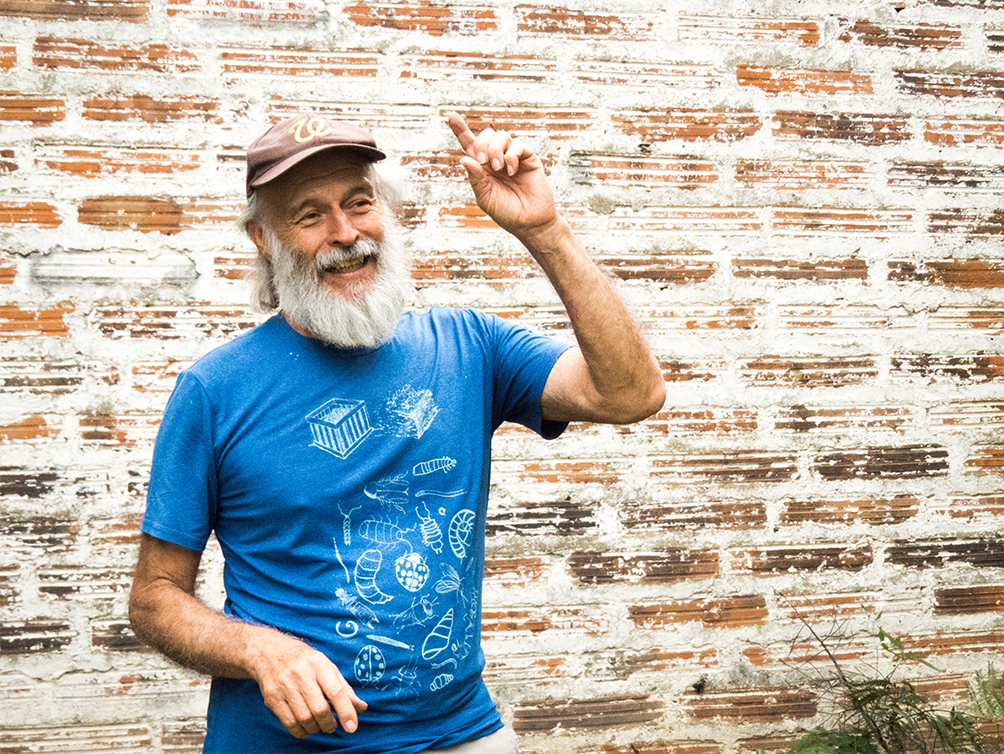 An older man, turned diagonally toward the right side of the photo, smiles and raises his left arm, his index finger pointing up towards the sky. He has white skin, a full beard and moustache, and straight white hair. He is wearing a brown cap and a blue t-shirt with a white print. Behind him is a brick wall.