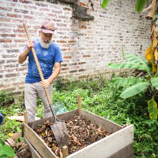 An older man with white skin and a full beard and moustache is holding a big shovel, with which he is working some dry leaves and dark earth in a square on the ground bordered by wooden slats. He is looking down at the earth. He is facing the camera and wears a brown cap, blue t-shirt and gray pants. Around him are bushes and low foliage. Behind him is a stained white brick wall.