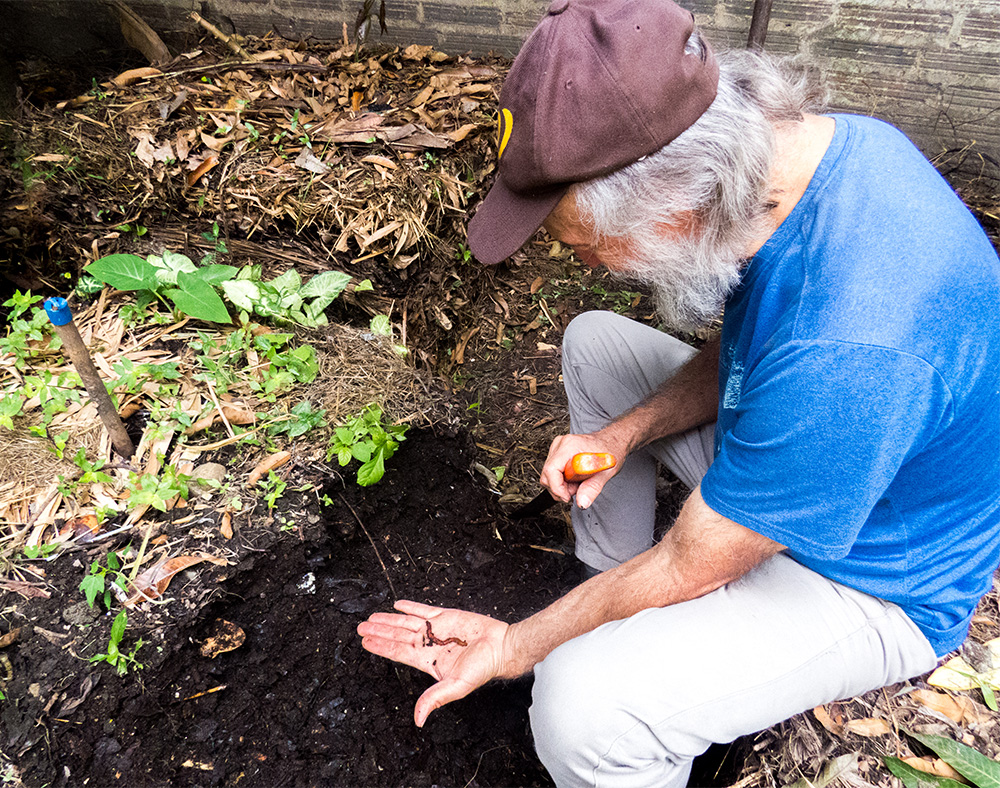 The same man from the cover photo, with white skin and full white beard and moustache, is sitting down facing the left side of the photo while displaying a worm on his left palm and sticking a machete into the ground with his right hand. He is wearing a brown cap, a blue shortsleeve t-shirt and gray pants. In front of him is a square hole dug into the earth. Around him his the ground, made of the same earth, covered by some dry leaves.