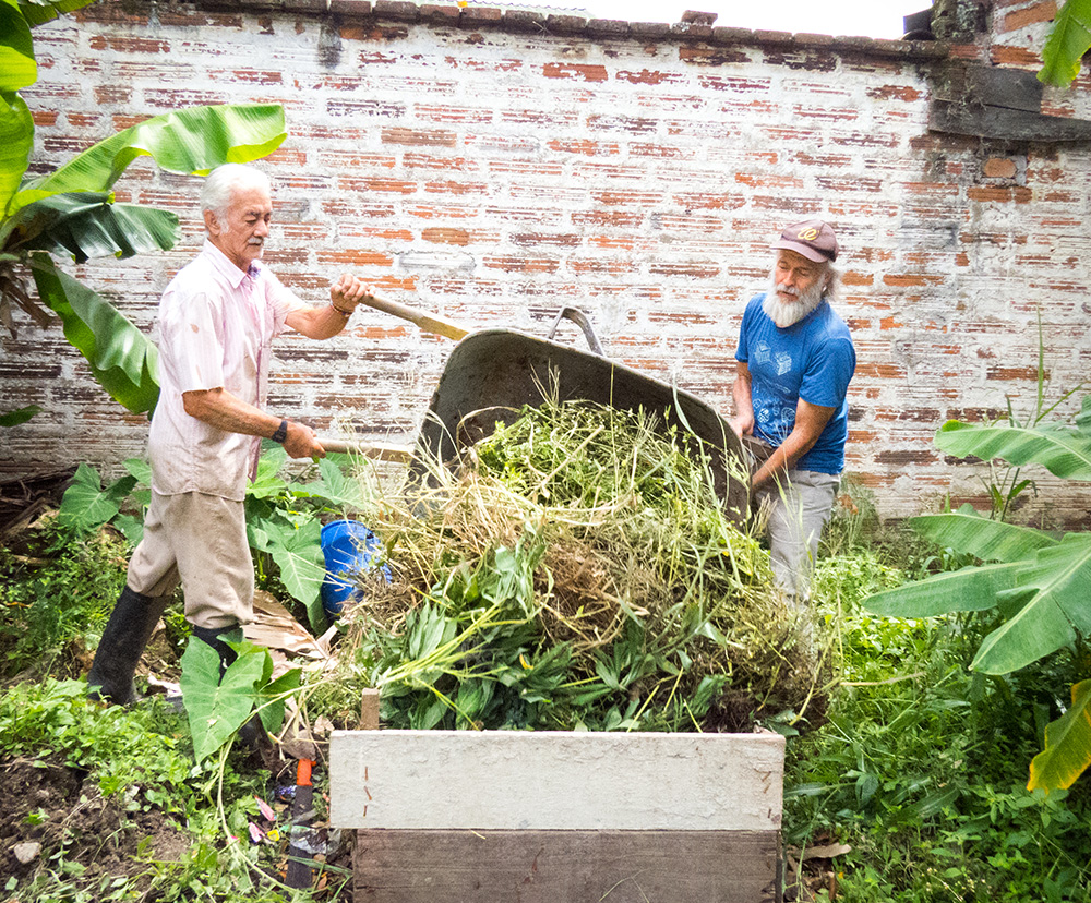 The same older man from the cover photo, with white skin, full beard and moustache, and straight white hair, is on the right side of the photo, helping another older man turn over a wheelbarrow, which is placed between them, facing the camera, and is dumping its contents into a square area bounded by wooden slats. The contents of the wheelbarrow are a large volume of leaves and green branches. The older man on the left of the photo has white skin, straight white hair and moustache, and is wearing a light pink shirt, beige pants and black rubber boots. They are surrounded by bushes and low foliage. Behind them is a stained white brick wall.