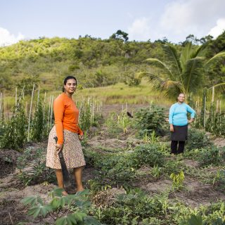 Two women are looking at the camera. The one towards the left side of the photo has her body facing to the right and is smiling slightly. She has dark skin and dark brown curly hair tied back. She is wearing a white knee-length skirt with orange and red flower print, an orange long-sleeved shirt, and is holding a machete in her right hand. The other woman is standing further back, resting her left hand on her hips. She has white skin and has her brown hair tied back. She is wearing a black knee-length skirt over black pants and a bright blue long sleeve shirt. Around them is dirt ground and low foliage. In the background, a grassy plain and light blue sky with a few clouds.