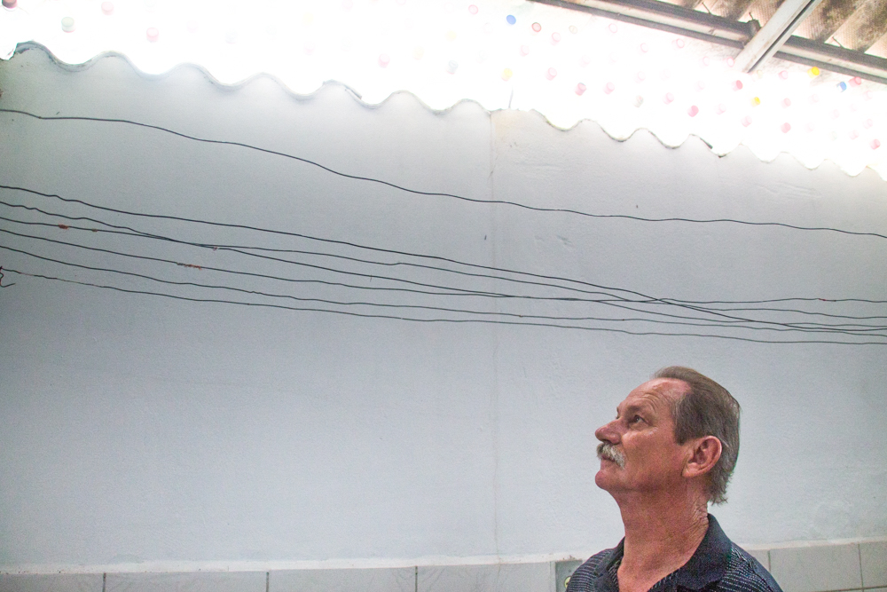 The same man from the cover photo, with white skin, gray hair and moustache, appears in profile in the lower left corner of the photo, looking towards a white wall in the back of the photo, on top of which is a section of roof tiles with clear plastic bottles stacked on top, the bottle caps facing the camera. In front of the wall, where the man is looking, are black wires running horizontally across the photo, just below the section of roof tiles.
