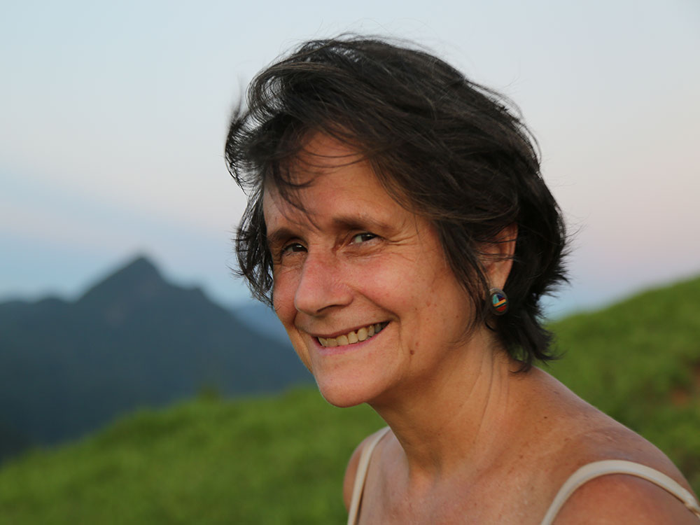 A woman facing the left side of the photo looks at the camera and smiles. She has white skin, straight brown hair, and wears a colorful circular earring and a white tank top. In the background, a valley of grassy ground and, in the background, the countenance of a hill and the blue-gray sky.