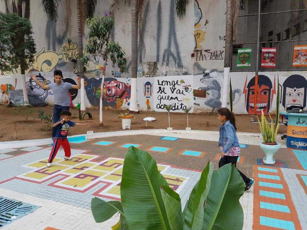 """Duas crianças e um jovem adulto brincam na amarelinha pintada ao chão de uma praça. O jovem adulto e o menino estão do lado esquerdo da foto, e a menina ao lado direito. O menino pisa nos números 1 e 2 da amarelinha, e a menina observa. Todos usam roupas coloridas. Ao fundo, um muro grafitado com ilustrações de rosto e a frase """"Longe se vai quem acredita.""""."""