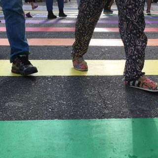 A photo of the feet of various people walking across a colorful pedestrian crossing.