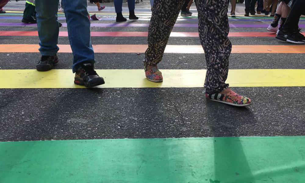 Os pés, calçados, de diversas pessoas, passando sobre uma faixa de pedestres colorida.