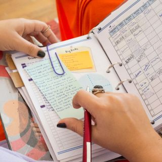 The hands of a white person, with the nails painted black and gold rings on some of the fingers, holds an open scheduling book with some notes attached to it with paper clips. The person is holding a red metal pen with their right hand. In the background are the person's legs, in orange pants, and a wooden floor.