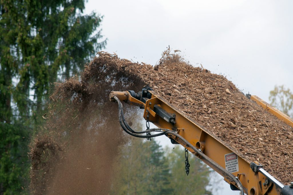 A yellow metal machine sticks up from the lower right corner of the photo, spewing wood chips into the air. In the back are the dark leaves from the top of a few trees and a gray sky.