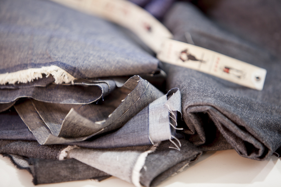 Close-up of dark gray jeans fabric folded up, with the tips bunched up.