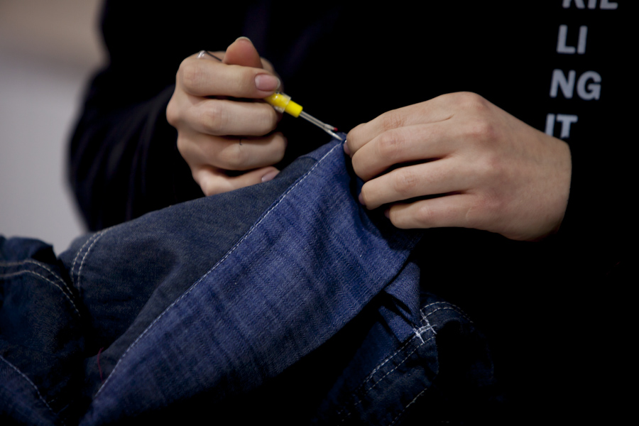 A white person's hands are handling some dark jeans with a sharp metal tool that is about the size of their fingers. In the background is the person's torso, wearing a black sweatshirt with some white letters sewn into the chest.