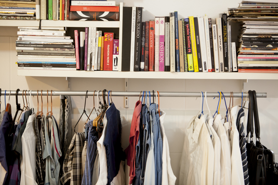 The photo shows a white wall with a shelf, facing the camera, full of books. Below the shelf are some items of clothing hanging on hangers along a silver metallic tube.