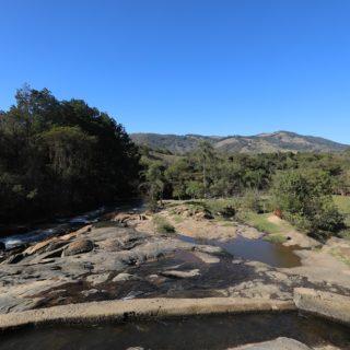 Um chão de pedras escuras é cercado por um riacho, pelo lado esquerdo, e por áreas arborizadas, à frente a à direita. Ao fundo, o semblante de um planalto, com variações de tons de verde, e o céu azul claro, sem nenhuma nuvem.