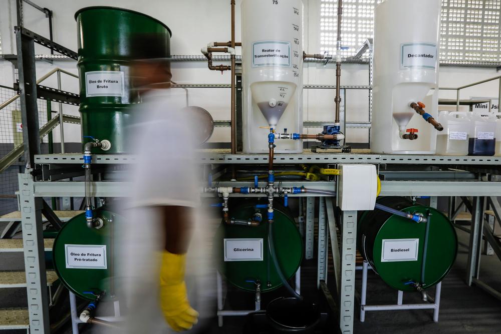 Uma pessoa passa em frente a barris verde bandeira e grandes recipientes brancos translúcidos, em um laboratório industrial. A pessoa usa roupas brancas e luvas de borracha amarelas, sua imagem está desfocada.