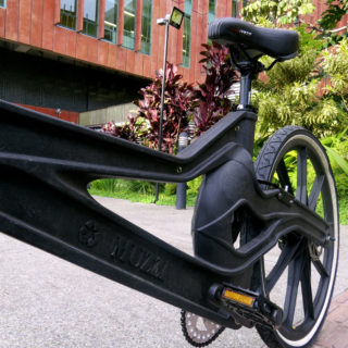 The photo shows the seat and back wheel of a black bicycle on a street, facing the camera diagonally from the left corner. In the back is a building covered with brick-colored tiles and, to the right, a garden with some short trees.