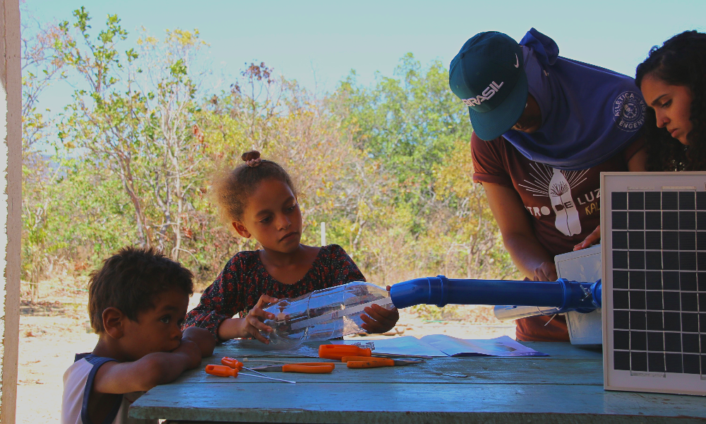 A boy rests his crossed arms on a wooden bench. Around the bench, a girl, a woman and a man are working on building a plastic bottle lighting fixture. In the back are some short trees and a bright, clear blue sky.
