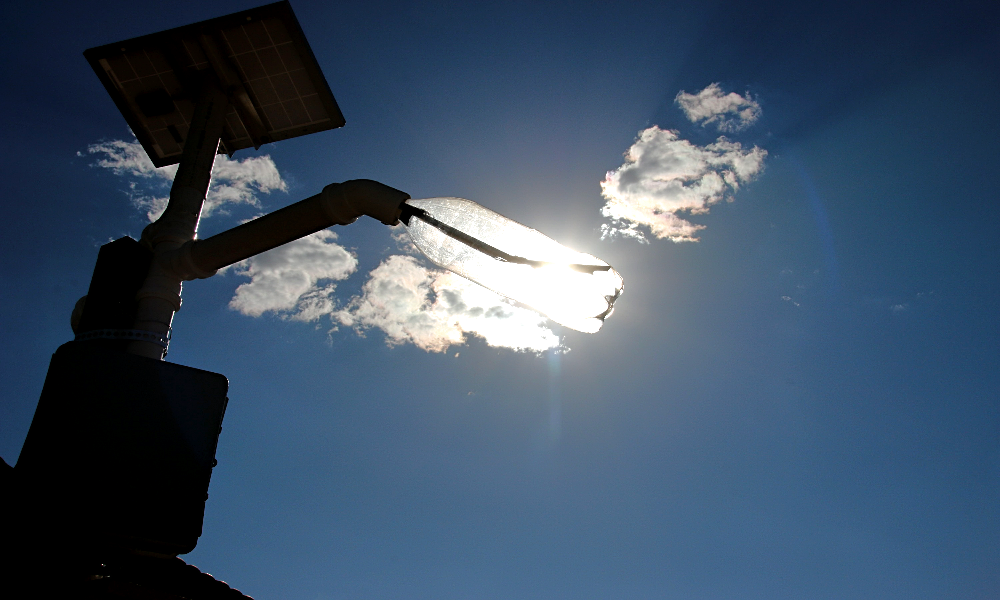 The photo shows a lighting fixture with a solar panel facing upwards, on the left corner of the image, and a pipe holding a plastic bottle lamp going towards the center of the photo. In the back is a bright blue sky and a few clouds.