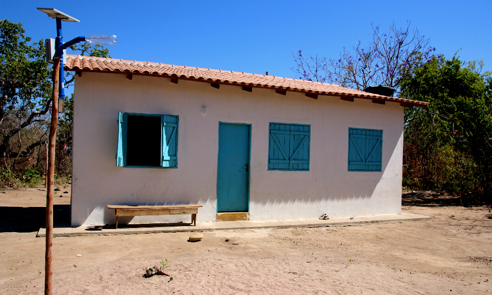 A plastic bottle lamp post in front of a one-floor house with white walls, orange roof and light blue wooden windows. The ground is made of dirt. In the back is a bright, clear blue sky.