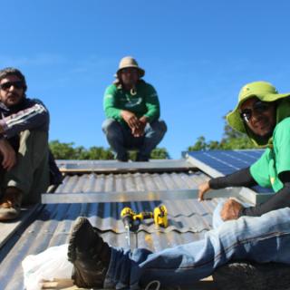 Três pessoas estão sentadas sobre um telhado de telhas metálicas prateadas, de frente para a câmera. Duas delas usam chapéus e camisetas verdes de mangas longas, as figuras estão desfocadas. Ao fundo, o topo de folhagens de algumas árvores e o céu, azul claro, sem nenhuma nuvem.
