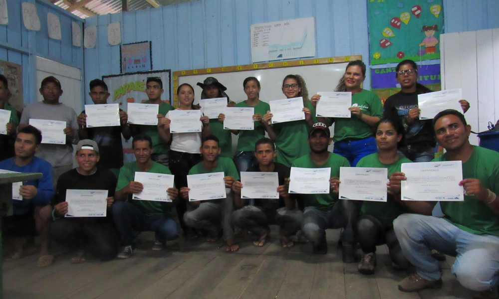 People wearing identical green t-shirts as a uniform pose for a photo holding up certificates. Behind them is a light blue wooden wall, with a whiteboard hanging on it along with some posters that are out of focus. The floor is made of dark wood.