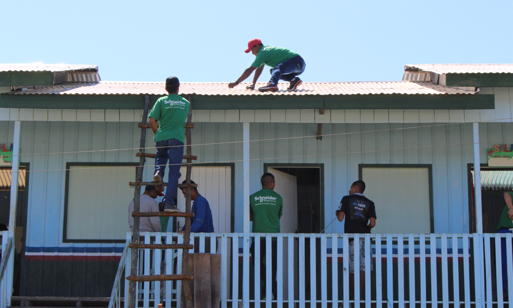 Men work on installing solar panels on a one-floor house with white wooden walls. One of the men is on the roof, squatting down and facing the left side of the photo. There is another man climbing up a rustic wooden ladder, towards the rooftop, with his back to the camera. The others are spread out around the area. Most of them are wearing identical green t-shirt as a uniform. The house has a white wooden fence on the edge of its front porch. In the background is a clear blue sky.