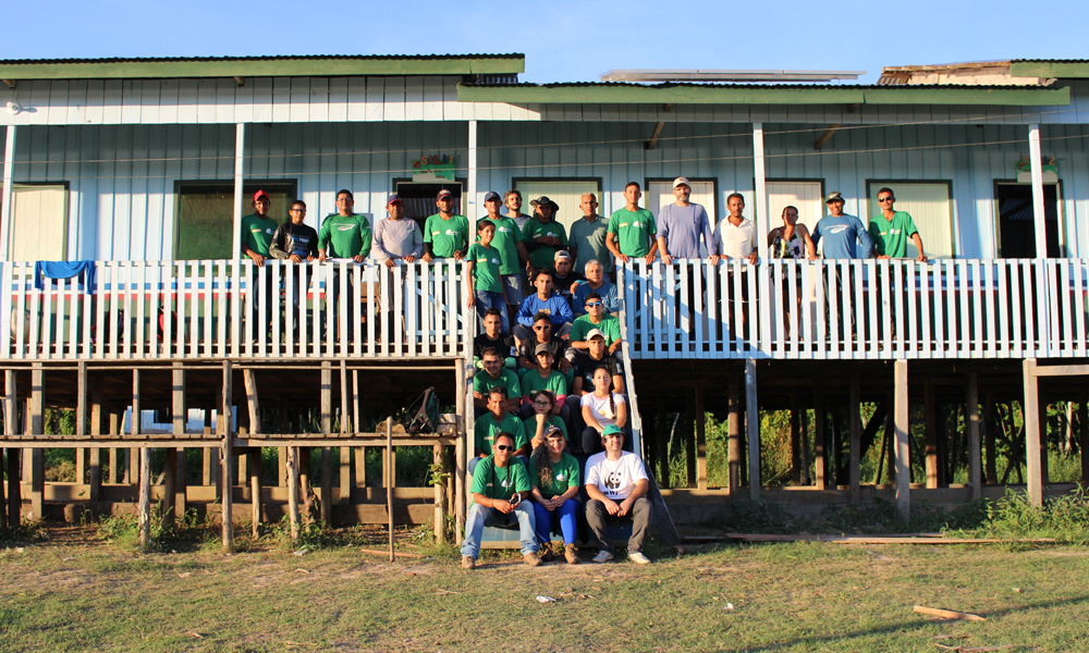 Workers wearing identical green t-shirts as a uniform pose for a photo, filling up the front stairs and porch of a white wooden house on stilts. The ground has short grass. In the background is a clear and sunny blue sky.