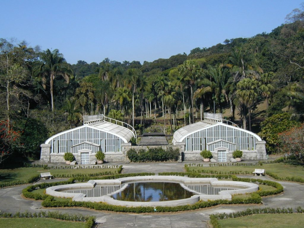 The photo shows two white architectural structures made of glass and metal, shaped into triangular domes. In front of them, closer to the camera, is a reflecting pool with white borders, surrounded by a gray cement walking path, which is further surrounded by small, trimmed bushes. In the background are palm trees and other tall trees.