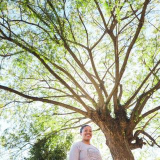 Uma mulher olha para a câmera e sorri. Ela tem pele negra e cabelos castanhos escuros presos em um coque, e usa uma camiseta cinza clara com uma estampa circular preta ao centro. Ao fundo, uma grande árvore de folhas claras e ramificações dispersas e o céu, azul claro.