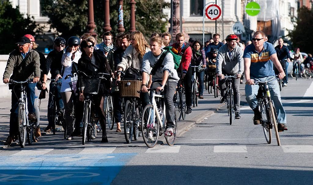 The photo shows a street packed with cyclists during daytime, all stopped in front of a traffic light, facing the camera.