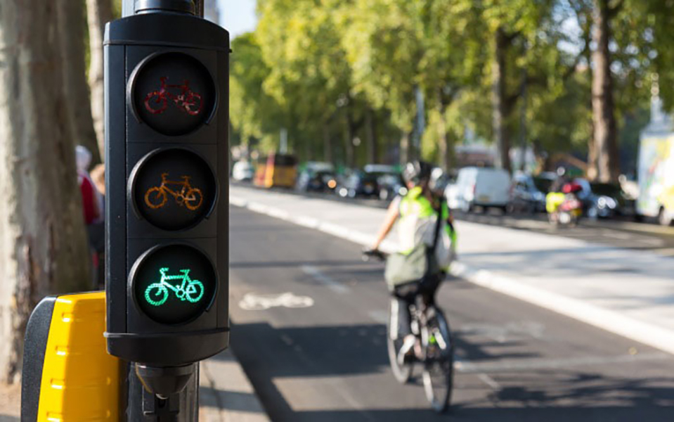 A traffic light with bicycle icons indicating go (green), that is, open for cyclists. In the background a cyclist rides on a bike lane towards the back of the photo. On the right side of the photo is a street with congested car lanes and, further to the right, a row of tall trees.