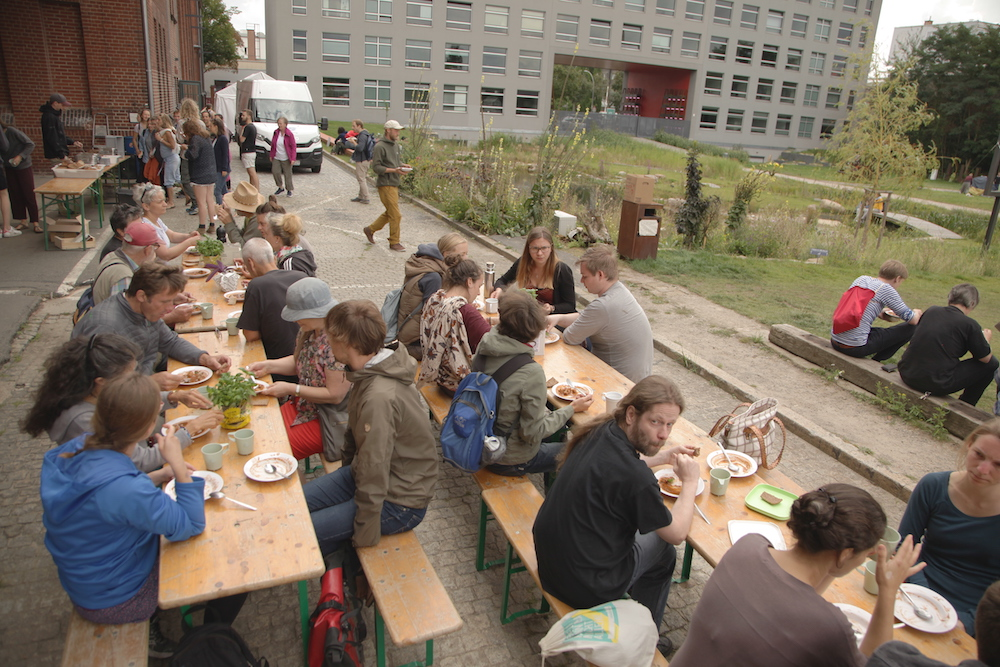 Various people are eating, seated on long benches around light colored rectangular wood tables. In the back are passersby, buildings, and a lawn. The ground beneath the tables is made of gray cement.