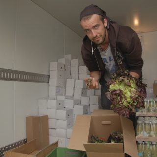 A man leans down towards the camera, showing a head of romaine lettuce in his hands. He has white skin, thin beard and straight, very light brown hair covered by a brown bandana tied around his head. He is wearing a gray t-shirt with blue print under an open brown jacket and dark jeans. By his feet is a cardboard box with some heads of romaine lettuce. Around him are boxes of various food items, stacked on the floor. On the edges of the photo are white walls.