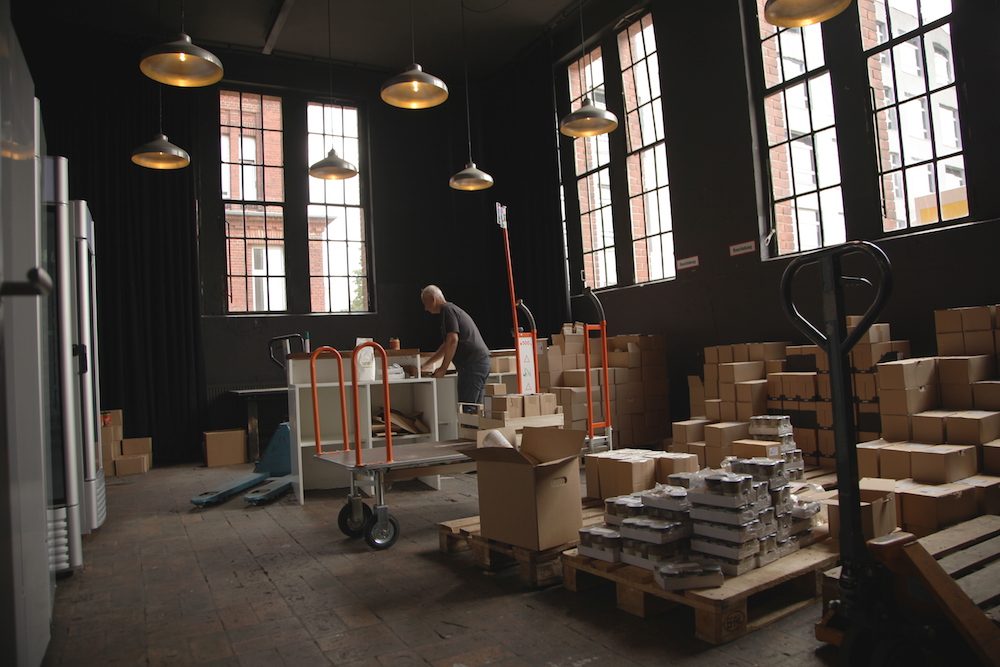 A man with his back to the camera is working inside a warehouse. Around him are closed cardboard boxes of various sizes, and shaded walls with large rectangular glass windows with dark wood frames. The floor is dark gray cement. At the top of the photo are light fixtures in a flattened bell shape hanging by wire with their lights on.