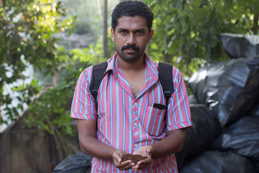 A dark-skinned Indian man with short black hair and black eyes is looking at the camera as he cups some black dirt in his hands. He is wearing a short sleeved pink shirt with light blue stripes. Behind him is a pile of black plastic bags to the right of the photo. Further back are some out of focus trees.